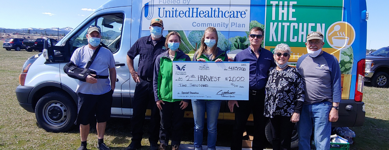 A group of people hold a $2,000 check in front of a van.